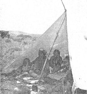 Southern Ute family under cloth shelter