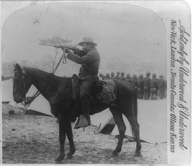 "Bankston Johnson - full blooded Choctaw Indian ""Rough Rider"" [on horseback aiming rifle]"