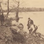 Pamunkey men digging clay on the river bank for pottery making. This is one of the traditional clay-holes of the reservation.