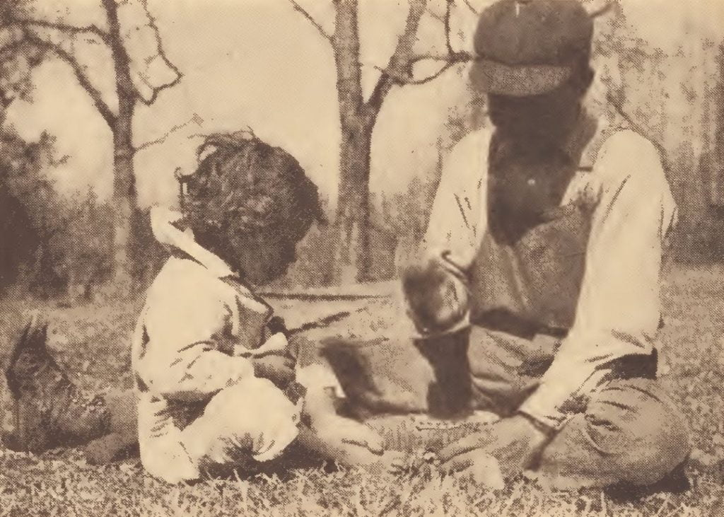 Chickahominy children cracking walnuts with stone mortar and pounder